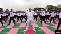 Премьер-министр Индии Нарендра Моди (в центре) принимает участие в массовом занятии йогой.