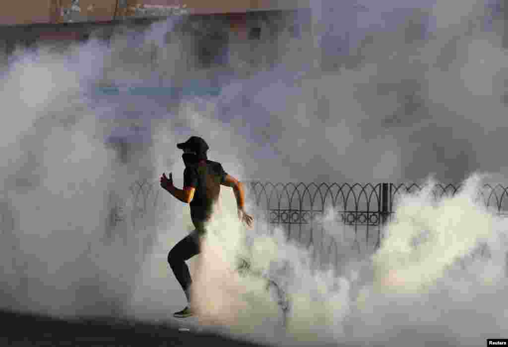A protester runs through a cloud of tear gas fired by Bahraini riot police during a protest in the village of Sitra, south of Manama. REUTERS/Hamad I Mohammed