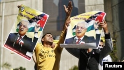 Gaza şäherinde geçirilen ýörişde adamlar prezident Mahmud Abbasyň portretlerini göterýärler, 29-njy noýabr.