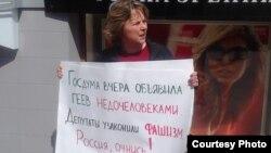 """Наталья Цымбалова, координатор «Альянса гетеросексуалов за равенство ЛГБТ», проводит одиночный пикет против """"антигомосексуального"""" закона."""