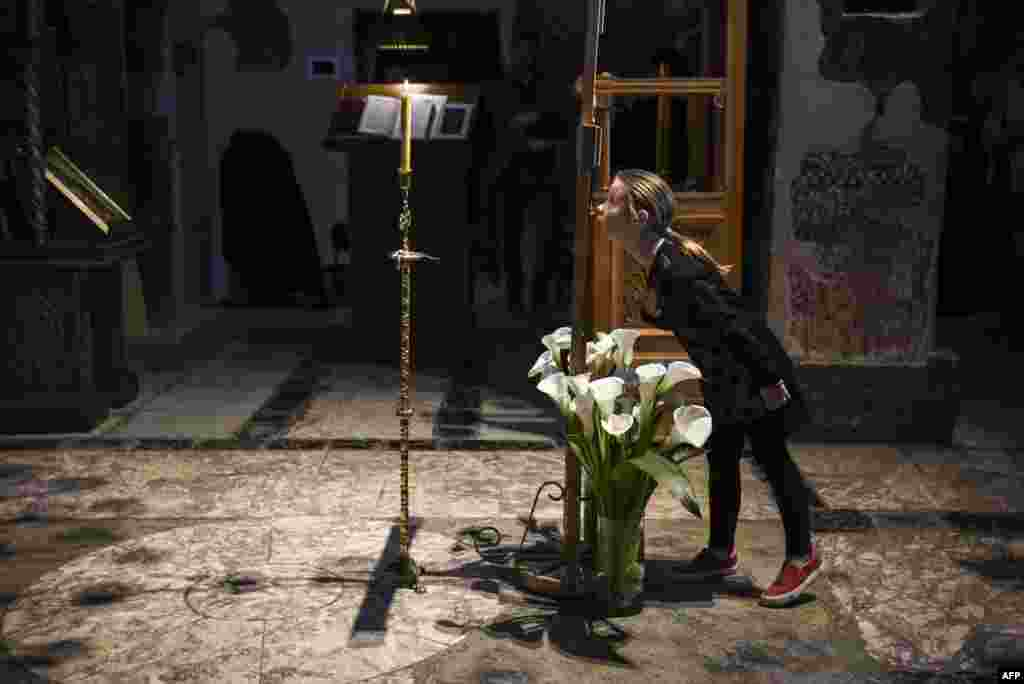 A young girl prays at the Gracanica medieval monastery in the town of Gracanica, central Kosovo. (AFP/Armend Nimani)