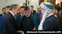 Former Afghan President Hamid Karzai (center) introduces the Taliban delegation to Russian Foreign Minister Sergey Lavrov (left) ahead of their meeting in Moscow on May 28.
