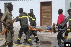 медики транспортируют человека, получившего ранения при взрыве в гостинице в Могадишо 20 февраля