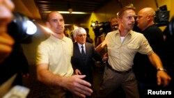 «Формула-1» жетекшісі, британ миллиардері Берни Экклстоун (ортада) көмекшілерімен бірге.