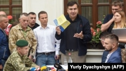 Mikheil Saakashvili speaks to the media while Ukrainian border guards try to hand him a protocol of administrative offense near the hotel where he is staying in the western city of Lviv on September 12.