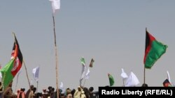 FILE: Supporters of the Taliban and Afghan government wave their respective flags during a cease-fire in June 2018.