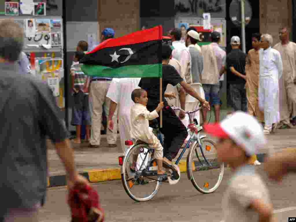 A young boy riding on the back of a bicycle holds his national flag in Tripoli on September 9. (Photo by AFP)