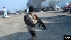 Сотрудник афганских сил безопасности на месте атаки на базу НАТО.