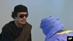 A grab from Libyan state television in early June shows Libyan leader Muammar Qaddafi greeting unidentified people at an unknown location.