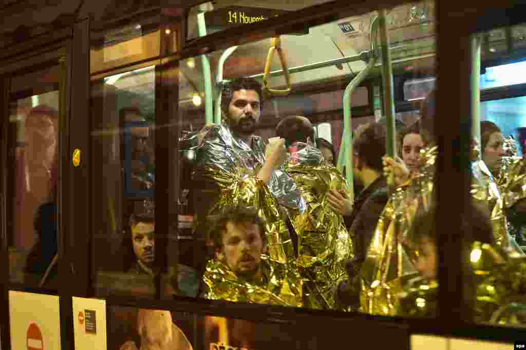 Survivors of the Bataclan theatre massacre wear emergency thermal blankets as they are evacuated by bus from the scene of the attack.
