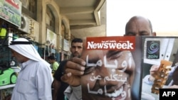 "A man browses through an Arabic copy of ""Newsweek"" in Baghdad on June 3."