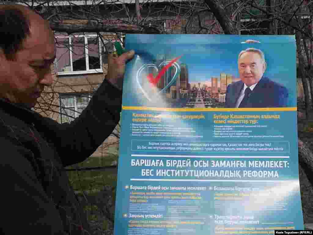 Мужчина с агитационной листовкой кандидата в президенты Нурсултана Назарбаева, действующего президента. Алматы, 8 апреля 2015 года.