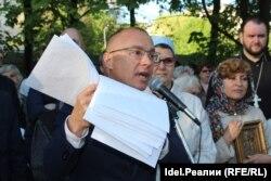 Василий Гвоздев показывает подписи в поддержку храма