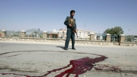 A police officer stands guard near bloodstains on the ground at the site of the bomb blast in Ghazni Province.