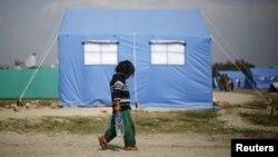 Житель одного из палаточных лагерей в Непале несет питьевую воду.
