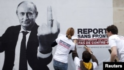 """Активисты организации """"Репортеры без границ"""" устанавливают плакат с изображением Владимира Путина как врага свободной прессы. Париж, 2013 год"""