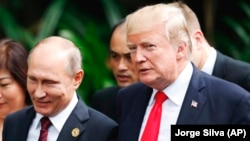 A file photo of U.S. President Donald Trump (right) and Russian President Vladimir Putin at the APEC Summit in Vietnam last year.