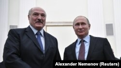 Russian President Vladimir Putin (right) poses for photographers with his Belarusian counterpart Alyaksandr Lukashenka during a meeting at the Kremlin in Moscow on December 25.