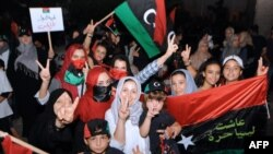 Women and children, mostly Libyans, gather outside the Libyan Embassy in Tunis on August 21, where the insurgents' flag was hoisted on the roof of the building.