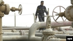 An Iraqi security guard walks along a pipeline at a refinery near the Umm Qasr port in the southern city of Basra.
