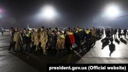Президент України Петро Порошенко (попереду) разом зі звільненими з полону бойовиків на Донбасі, 27 грудня 2017 року
