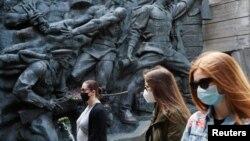 چند شهروند اوکراینی، ماسک بر صورت، در حال بازدید از موزه جنگ جهانی دوم؛ شنبه ۲۰ اردیبهشت