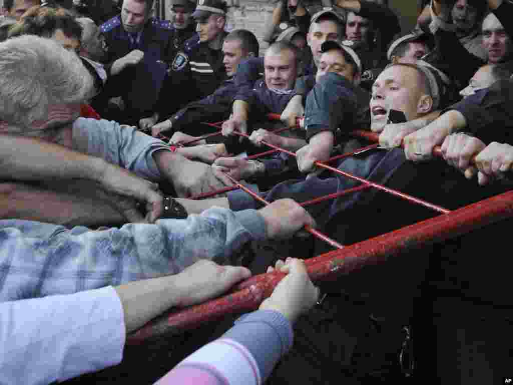 Police officers try to restrain supporters of Yulia Tymoshenko outside a Kyiv court. (AP photo/Sergei Chuzavkov)