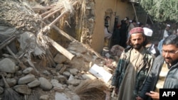 Islamic students gather at a destroyed religious seminary belonging to the Haqqani network after US drone strike in the Hangu district of Khyber Pakhtunkhwa province, November 21, 2013