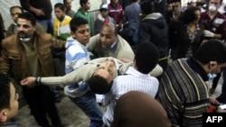 Раненого участника акции протеста несут в больницу. Каир, 20 ноября 2011 года.