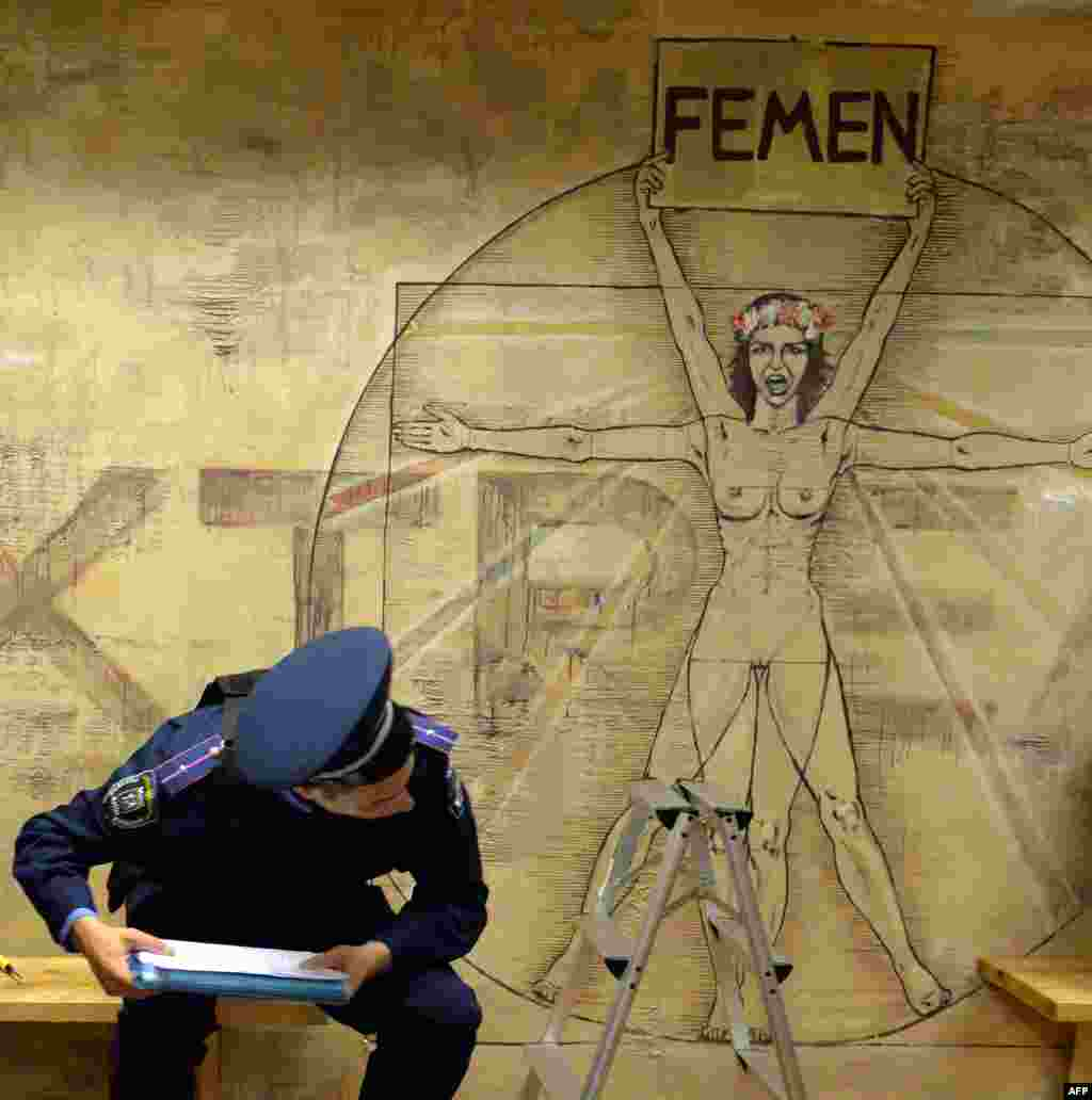 Ukrainian police search the premises of the feminist movement Femen in Kyiv. Police say they found a gun, a grenade, and portraits of Russian President Vladimir Putin and Patriarch Kirill. Anna Hutsol, leader of the organization, says it was a provocation organized by the security services against the activists of the organization. (AFP/Sergei Supinsky)