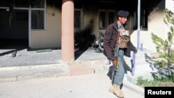 An Afghan policeman outside the government district building after a Taliban attack in the Khawaja Omari district of Ghazni Province on April 12.