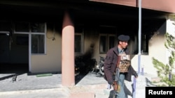 FILE: An Afghan policeman walks at the government district building after a Taliban attack in Khawaja Omari district of Ghazni province in April.