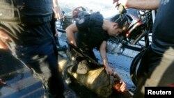 Полицейский осматривает избитого толпой солдата-мятежника.