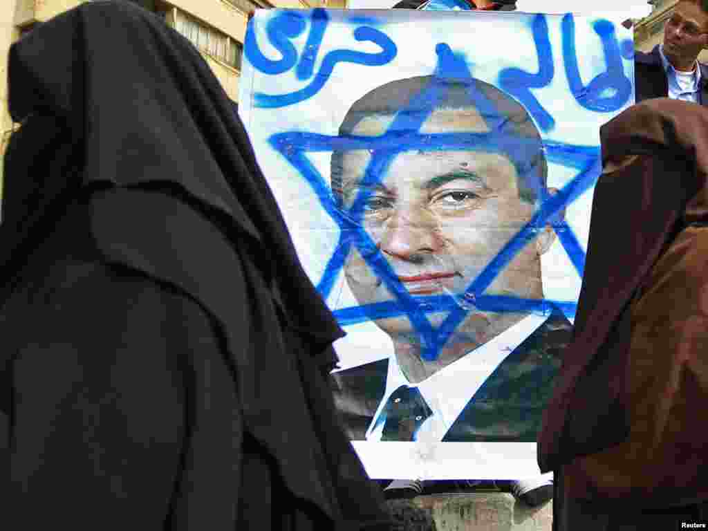 Women walk past an opposition supporter holding a poster of Mubarak painted with the Star of David.
