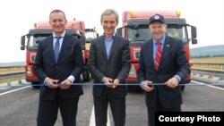 Посол Уильям Мозер (справа) на церемонии открытия отремонтированной дороги вместе с премьером Юрие Лянкэ (в центре)