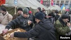 Тәуелсіздік алаңында билікке наразылық шеруіне қатысушылар тегін тамақпен жүрек жалғап тұр. Киев, 20 желтоқсан 2013 жыл.