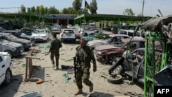 Afghan security personnel walk through the site of a suicide car bomb attack targeting a NATO convoy near the airport in Jalalabad on April 10.