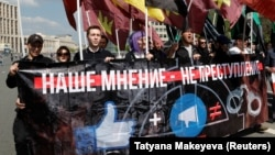 "People carry a banner reading ""Our opinion is not a crime"" during a rally against a court decision to block the Telegram messenger service in Moscow on May 13."