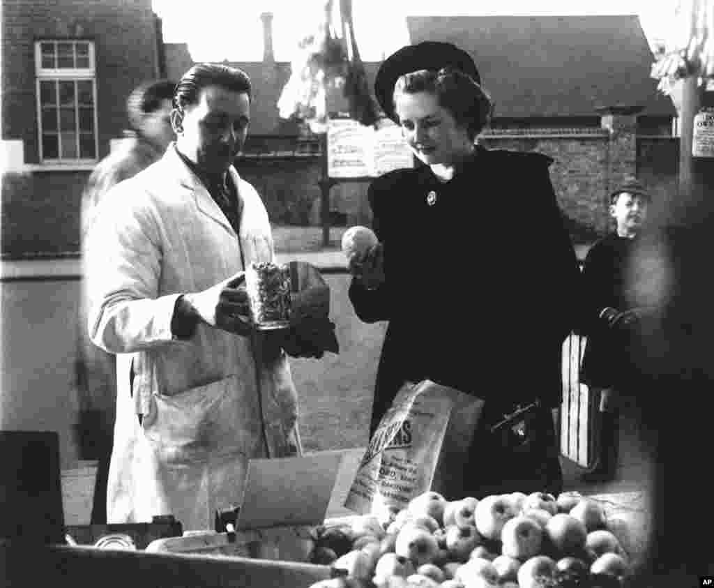 Margaret Roberts (later British Prime Minister Margaret Thatcher) buying peanuts and fruit in Kent in 1950
