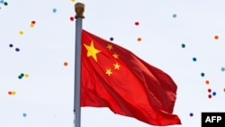 China -- Released balloons float over the Chinese national flag during a military parade over Tiananmen Square in Beijing on September 3, 2015
