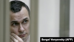 Ukrainian film director Oleg Sentsov stands inside a defendants' cage during a hearing at a military court in the city of Rostov-on-Don in July 2015.