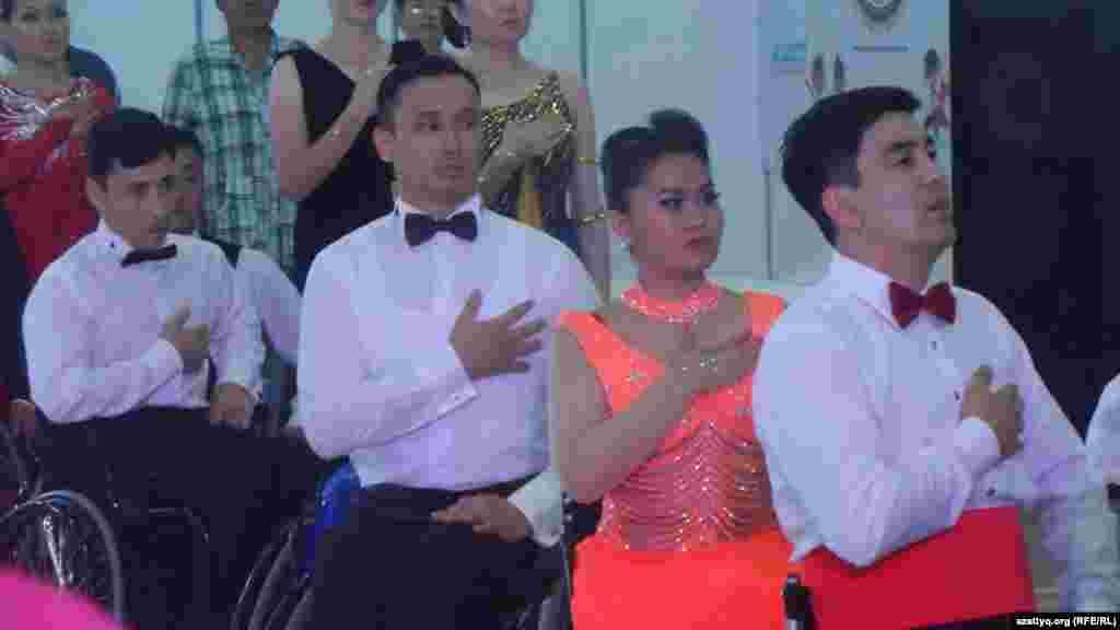 Участники соревнований слушают гимн Казахстана.