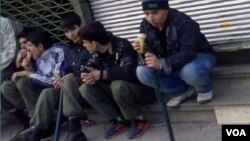 Young members of the Basij militia display their truncheons as they sit streetside and eat ice cream in an undated photo from Iran.