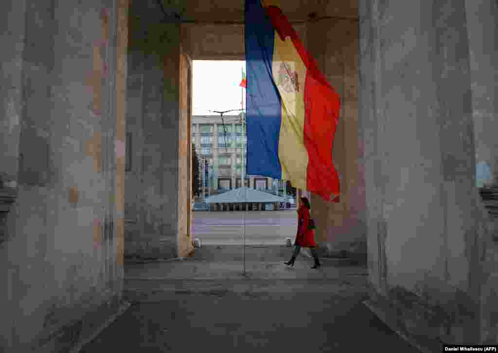 A woman walks under the Triumphal Arch next to the Moldovan flag in Chisinau.