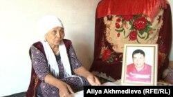 Зейнеткер Мағира Жұмағұлова ұлының портретінің қасында отыр. Алматы облысы, 2015 жылдың қазаны.
