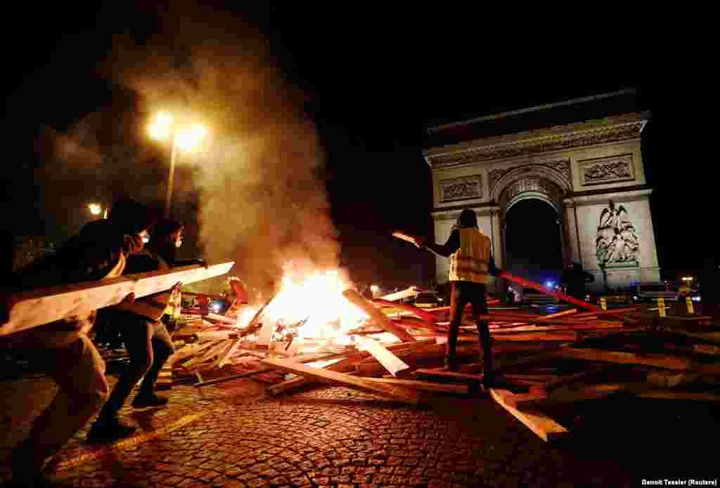 Протестуючі запалюють багаття під час протестів так званих «жовтих жилетів» на Єлисейських полях у Парижі, Франція, 24 листопада. Протести розпочалися з вимоги до влади відмовитися від збільшення податків на автомобільне пальне.(Reuters/Benoit Tessier)