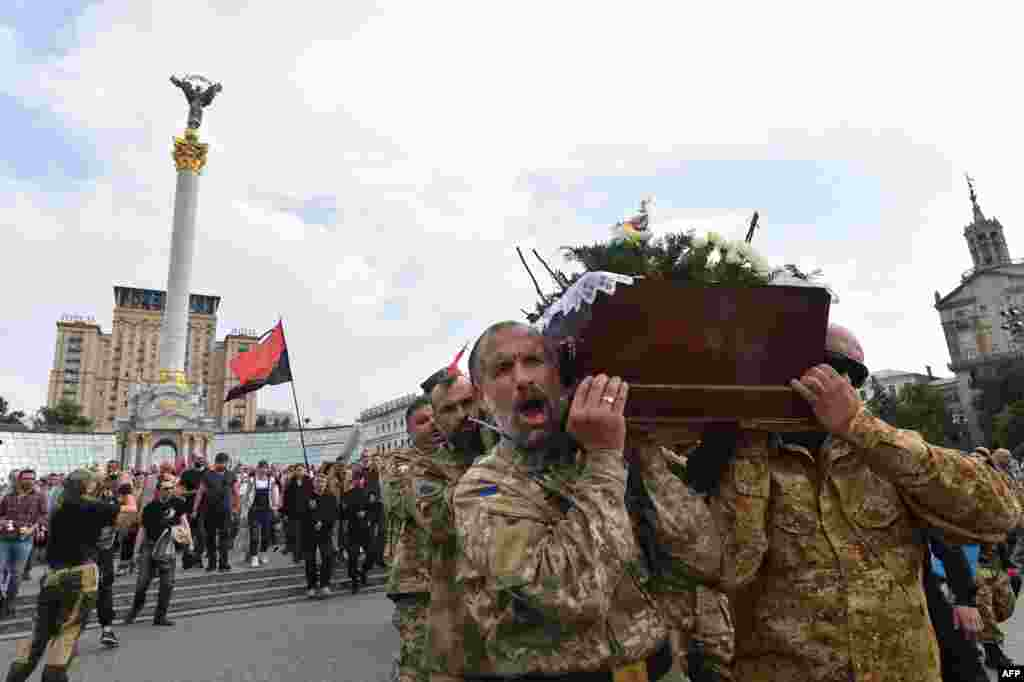 Fighters of the Ukrainian Right Sector volunteer battalion carry coffins with the bodies of their fallen comrades Yuriy Gnatyuk and Robert Masley during a funeral ceremony in Kyiv. (AFP/Sergei Supinsky)