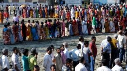 Voters line up to cast their votes outside a polling station during the first phase of general election in Alipurduar district in the eastern state of West Bengal on April 11.