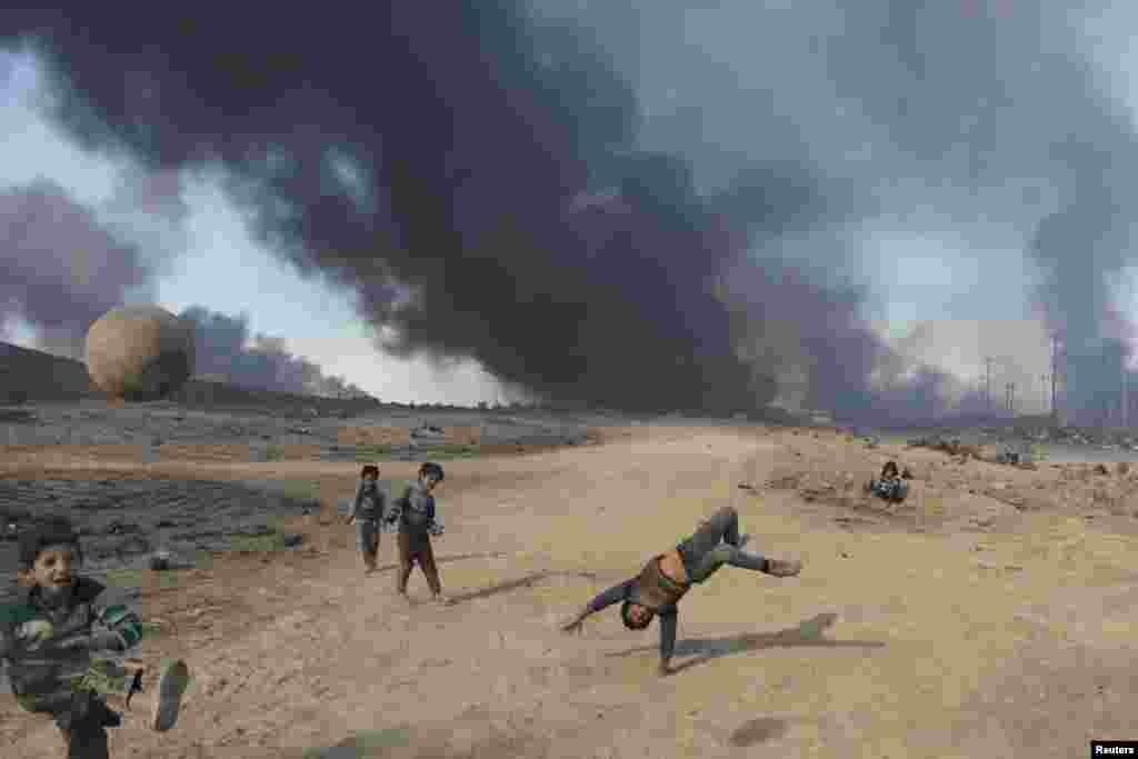 Дети играют в мяч на поле, за которым видны клубы дыма от горящего месторождения Кайяра.