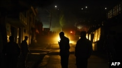 Afghan policemen stand guard at the site of a suicide attack at a foreign guesthouse in Kabul on November 27.